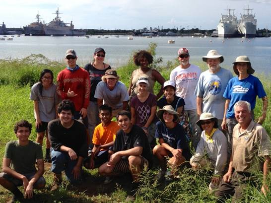Group photo of volunteers at the Waiawa Wetlands.  Middle Loch in the background