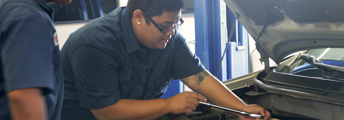Automotive students working under the hood on an engine