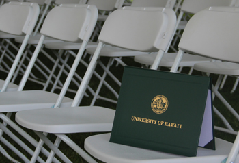 Leeward CC diploma cover positioned on a white chair at the commencement ceremony