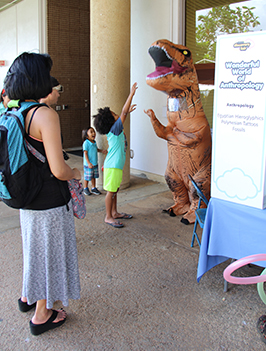 A Fair guest appearing in an inflatable T Rex costume