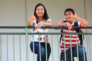 two students share a shaka while standing by the railing.jpg