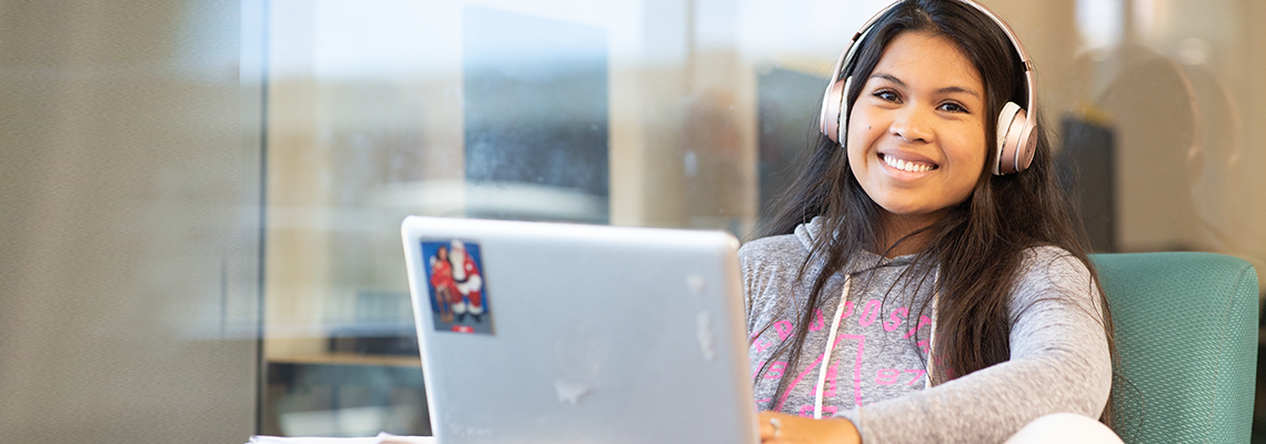 smiling student wearing headphones, studying with a laptop