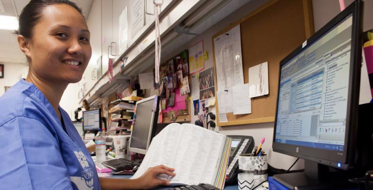 female medical biller at computer