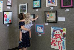 A Proud Mom holds your daughter to get a closer look at her artwork on display