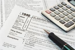 Income tax forms with a pen and calculator