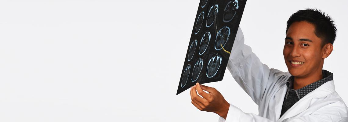 Pre-med student in lab coat examines brain scans