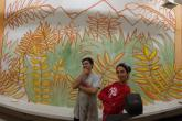 Students pose in front of the work in progress