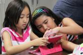 Young girl helps another young girl with an app on her tablet