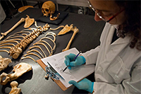 forensic student with skeleton in lab