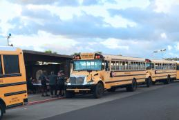 Shuttle busses line up in the center of campus parking lots