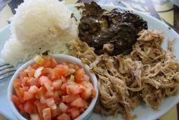 a dish of kalua pork, mini laulau, rice and lomi salmon