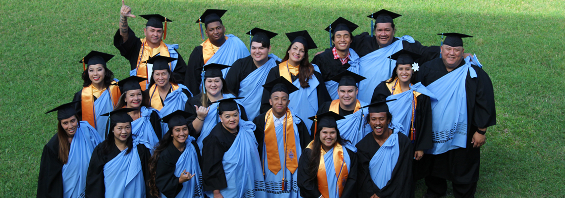 group of happy grads at commencement with college kihei and several wearing PTK stoles