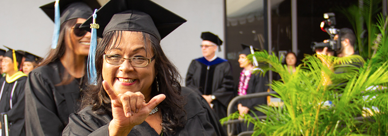 female at graduation showing shaka to camera