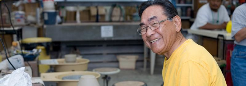 older man sitting at ceramic wheel smiling at camera